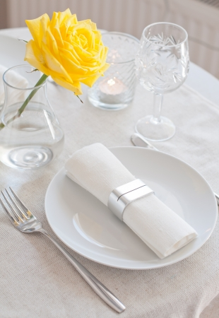 An elegant dining table setting with a white cloth and a yellow rose