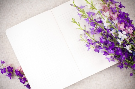 Open notepad and a bouquet of purple wildflowers closeup