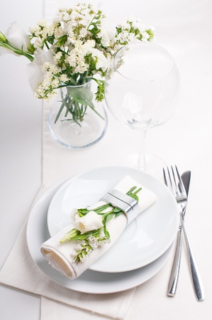 Festive table setting and decoration with fresh flowers in white colors