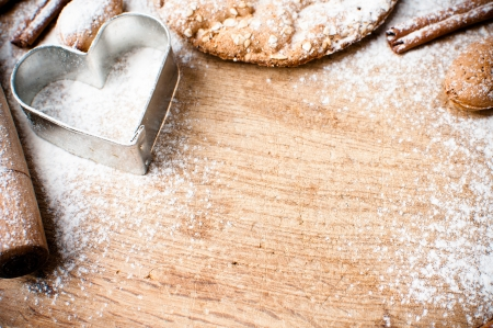 Christmas and holiday baking background, flour, bakeware, heart, cinnamon, cookies and almonds on a wooden board, viewed from above