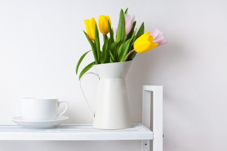 home interior decoration  a bouquet of tulips in a jug and a cup and saucer on white shelves