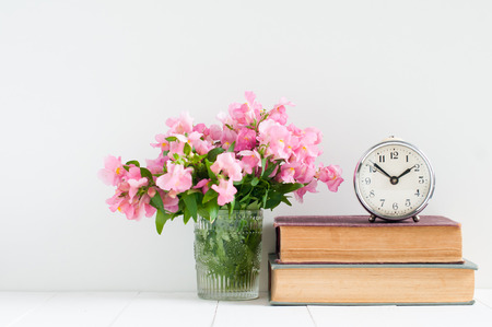Retro home decor: a stack of books, flowers and a vintage alarm clock on a white wall shelf
