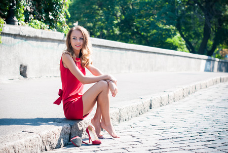 Beautiful young slim woman on an empty city street, lady in red dress and high heels has fun, sitting on a pavement barefoot without her shoes, smiling