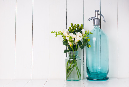 Vintage home decor, ancient turquoise siphon, freesias bouquet and bottles on a white wooden background.