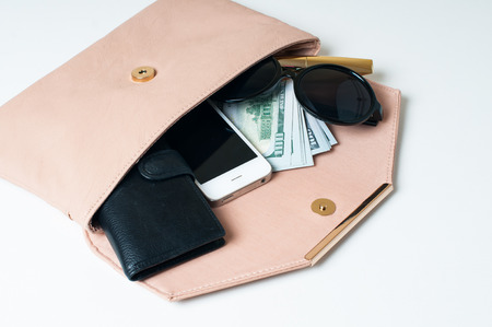 Cosmetics, sunglasses, money, purse and smartphone in an open beige woman's clutch handbag on a white background.