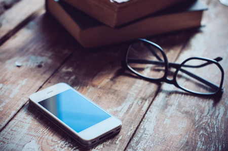 Old vintage books, smartphone and glasses on a wooden table
