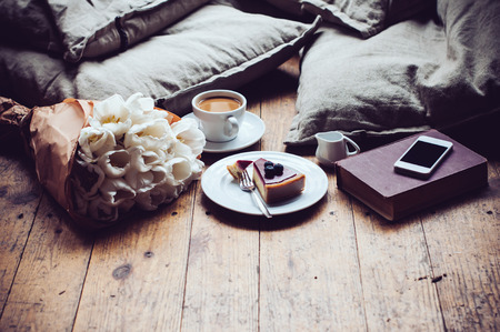 Pillows, a bouquet of tulips, coffee with milk, cheesecake and smartphone on a shabby wooden floor. Hipster lifestyle