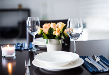 Simple home table setting, glasses and cutlery, roses in a vase.