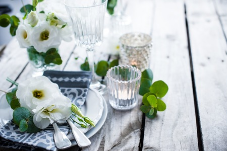 Photo pour Table setting with white flowers, candles and glasses on old vintage rustic wooden table. Vintage summer wedding table decoration. - image libre de droit