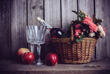 Rustic still life, fresh natural pink roses in a wicker basket  and a bottle of rose wine with two wineglasses and nectarines on an old wooden barn board background. Flowers and fruits for vintage wedding.