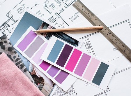 Interior designer's working table, an architectural plan of the house, a color palette, furniture and fabric samples in grey and pink color. Drawings and plans for house decoration.