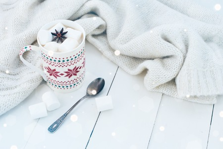 Cozy winter home background, cup of hot cocoa with marshmallow and star anise, old vintage books and warm knitted sweater on white painted wooden board background.