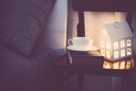 Cozy evening bedroom interior, cup of tea and a night light on the bedside table. Home interior decor with warm light.