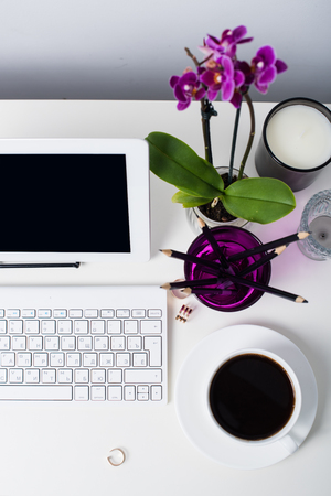 Young business woman workspace, white feminine office interior closeup, orchid flowers and laptop on a table.