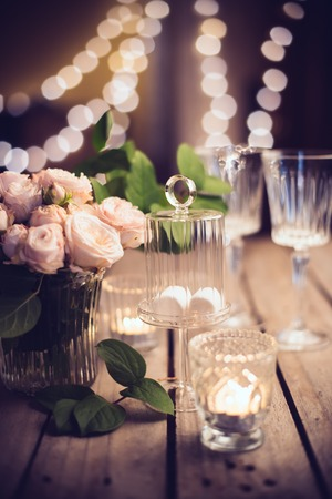 Photo for Elegant vintage wedding table decoration with roses and candles, warm night light filter - Royalty Free Image