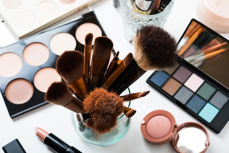 Professional makeup brushes and tools, natural make-up products set on white table.