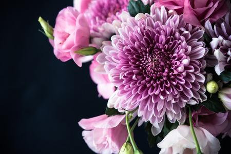Bouquet of pink flowers closeup on black background, eustoma and chrysanthemum, elegant vintage floral decor