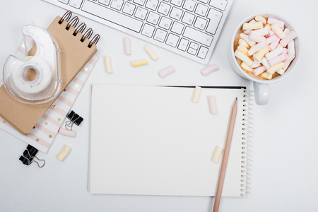 White feminine hipster workspace background, styled womans office table with coffee and marshmallows