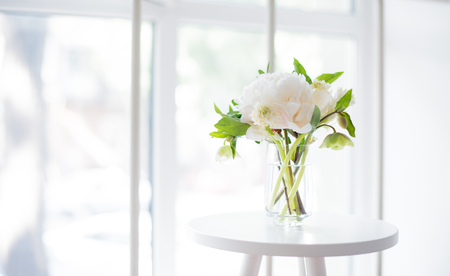 white peony flowers on coffee table in white room interior, brig