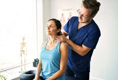 Photo pour Male Physical Therapist Stretching a Female Patient nack - image libre de droit