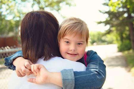 Photo pour A portrait of trisomie 21 child girl outside hugging his mother on a school playground - image libre de droit
