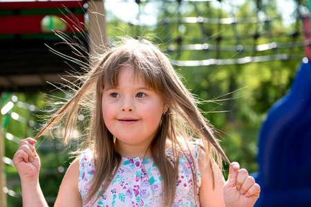 Photo pour A portrait of trisomie 21 child girl outside having fun on a park - image libre de droit