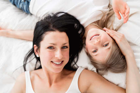 Photo pour Mother and daughter enjoy in bed at home - image libre de droit