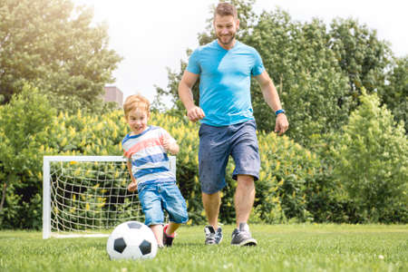 Photo pour Man with child playing football outside on field - image libre de droit
