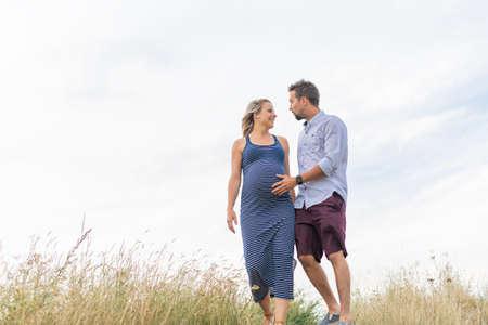 Photo pour pregnant woman at beach with husband having fun - image libre de droit