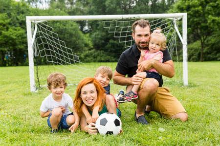 Foto de Happy family with football ball on a field - Imagen libre de derechos