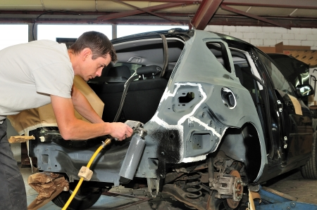 Car mechanic at work in body shop
