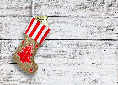 Photo for Red christmas boot with gifts on background wooden wall - Royalty Free Image