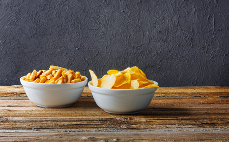 Photo for Salty snacks. Chips, crackers in bowls on wooden table on brick wall - Royalty Free Image