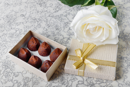 Beautiful white rose with golden gift box and chocolate truffles for Valentine's Day or wedding
