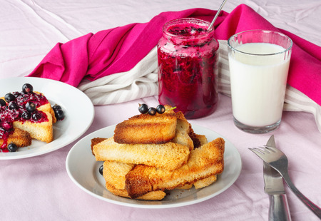 Photo pour Delicious toasts bread with homemade currant jam with milk on bright crimson tablecloth - image libre de droit