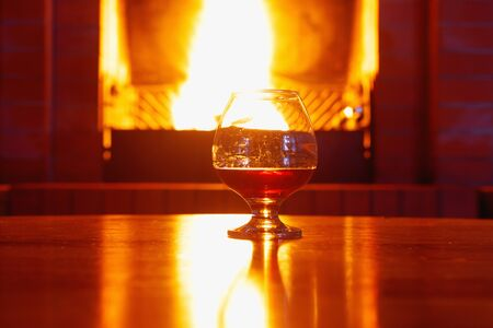 Photo pour One glass of cognac on background of old brick fireplace with  bright fire - image libre de droit