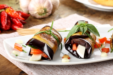 Eggplant rolls with cheese, tomato and basil on complex background