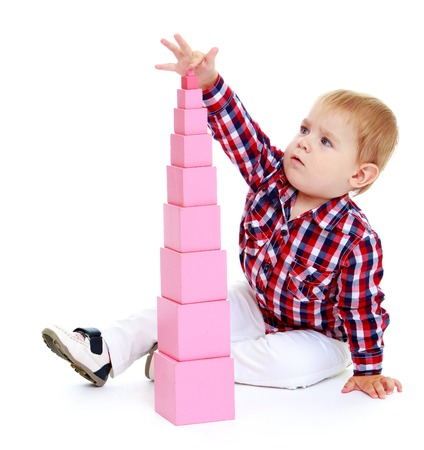 Photo pour Little boy puts cubes.Early years learning a happy childhood concept.Isolated on white background. - image libre de droit