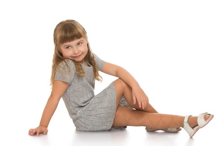 Beautiful Caucasian little girl with long blonde, flowing hair and short bangs, in a gray knitted dress with short sleeves. Girl sitting on the floor turning the camera sideways - Isolated on white background