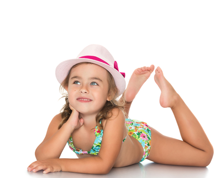 Photo for Adorable little girl in a pink hat and a bathing suit lying on the floor and looks up - Isolated on white background - Royalty Free Image