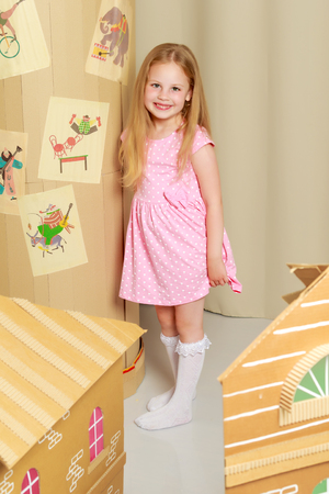 Photo for A little girl is playing in a cardboard house - Royalty Free Image