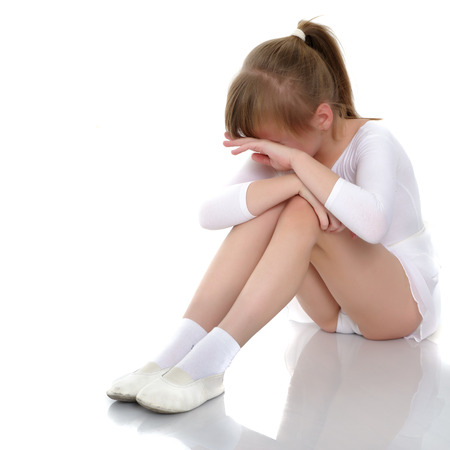 Photo for Girl gymnast sits on the floor and cries - Royalty Free Image