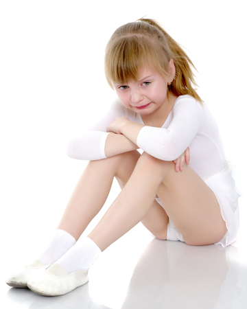 Photo pour Girl gymnast sits on the floor and cries - image libre de droit