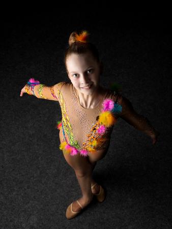 Girl gymnast on a black background