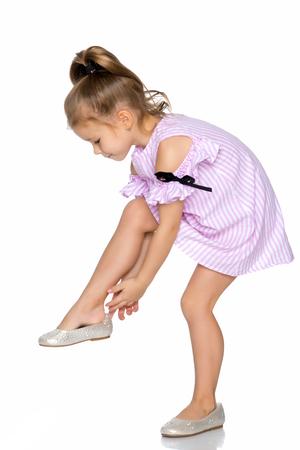 Photo pour The little girl puts on her shoes. - image libre de droit