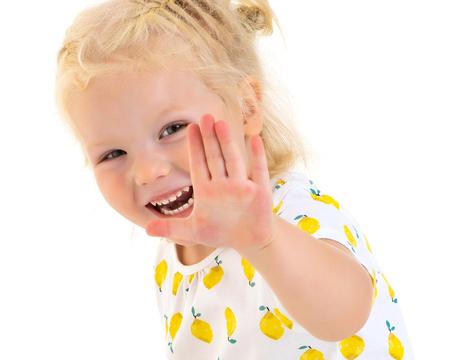 Foto de A happy little girl is waving her hand. - Imagen libre de derechos