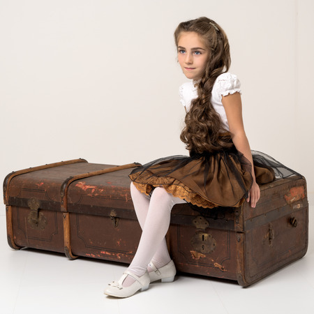 Foto per A little girl is sitting on a wooden box. - Immagine Royalty Free