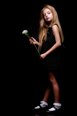 Foto de Little girl with a white flower on a black background. - Imagen libre de derechos