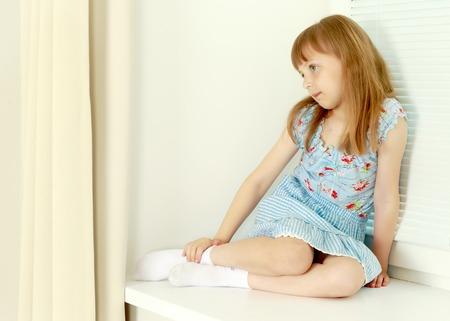 Photo pour A little girl is sitting by the window with jalousie - image libre de droit