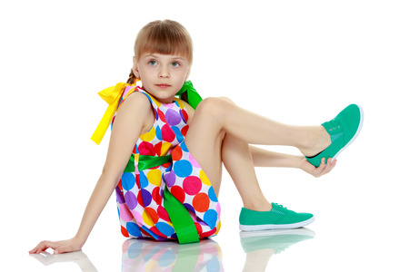 Photo for A little girl in a dress with a pattern from multi-colored circl - Royalty Free Image